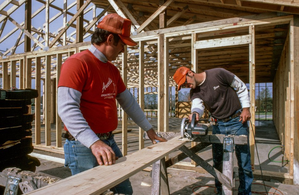Free image of Two Carpenters cutting a wood board using electric saw