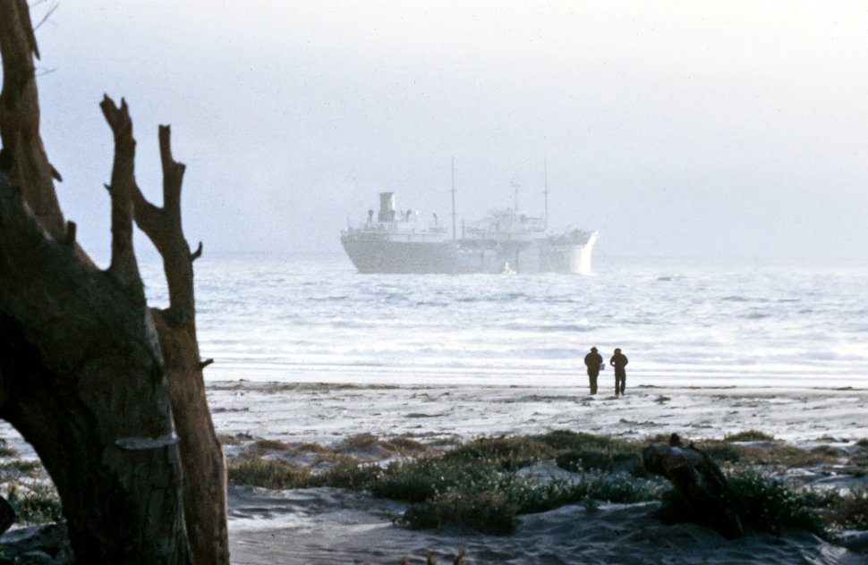 Free image of Long View of large ship crossing the ocean as two people watching it from the ground