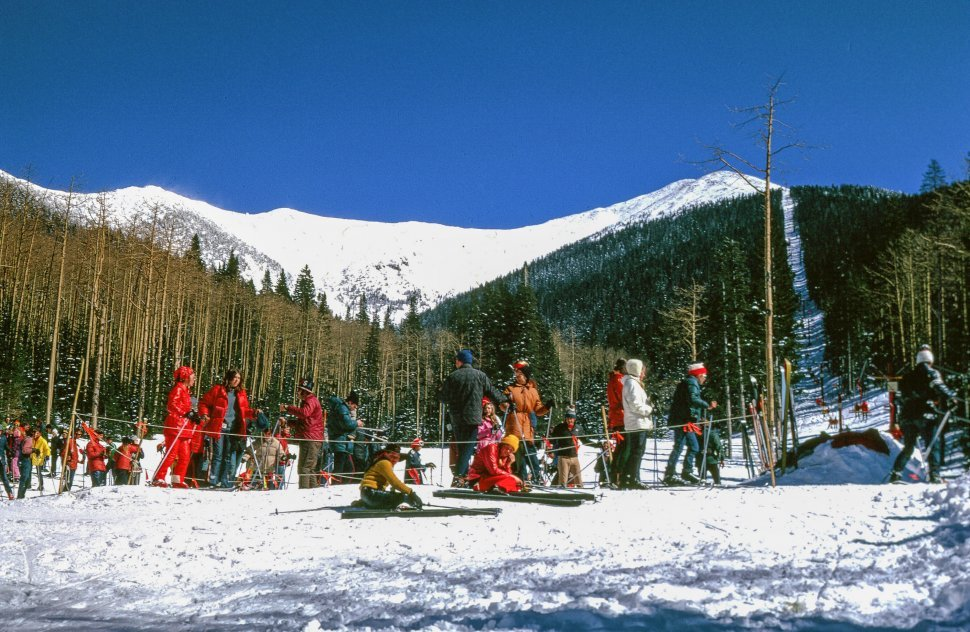 Free image of People stand before ski lift in queue