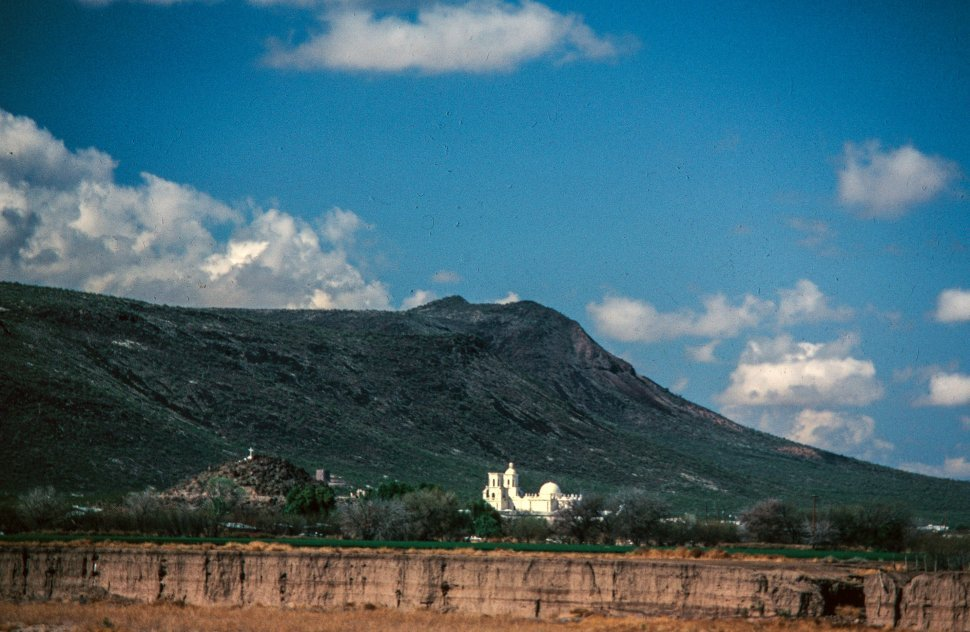 Free image of Long view of San Xavier del Bac as desert in foreground and mountain in the background, Tucson, Arizona