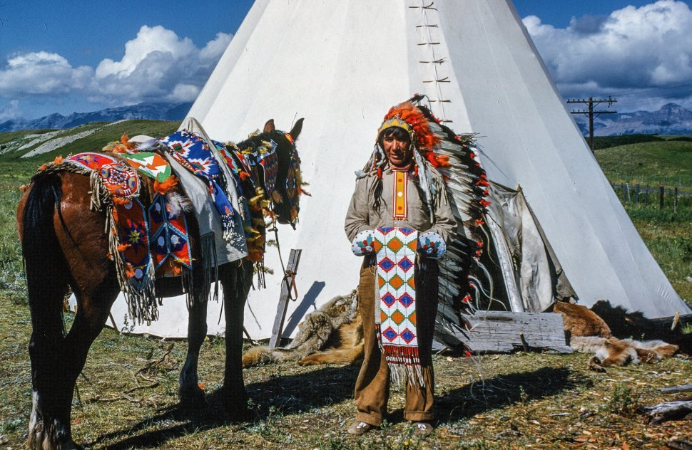 Free image of Native American woman standing outside Tipi with horse