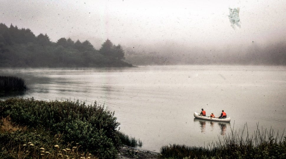 Free image of Three Kayakers wearing life saving jackets sitting in a boat in the river
