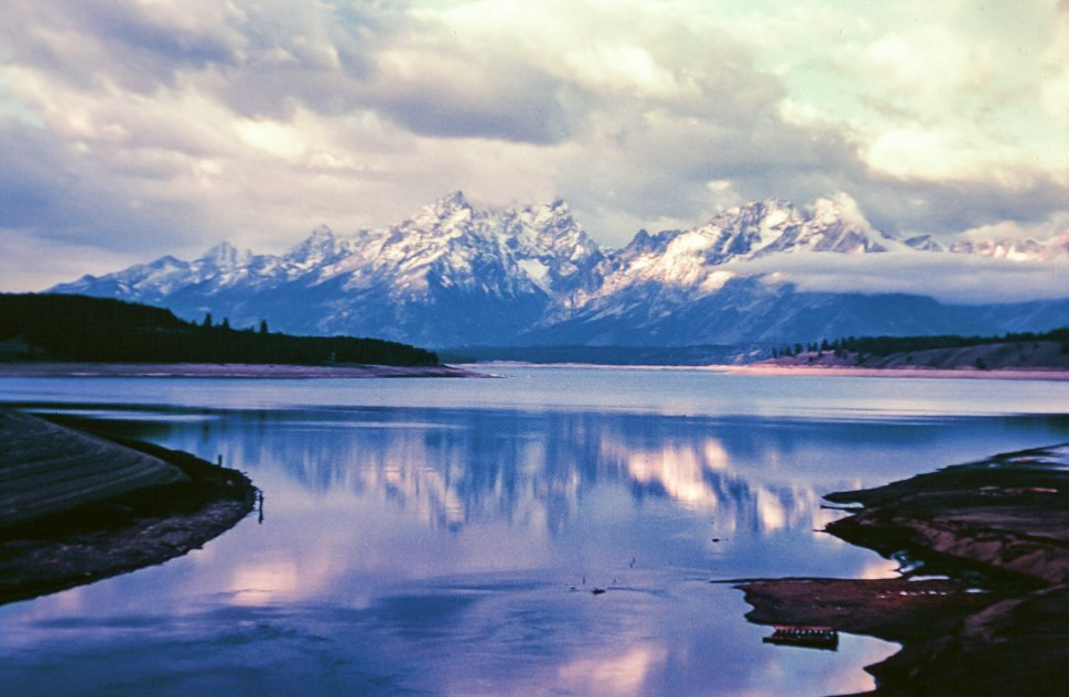 Free image of Reflection of evening clouds and snow capped mountains in the lake