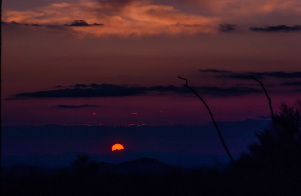 Free image of Sun going down over a mountain during sunset