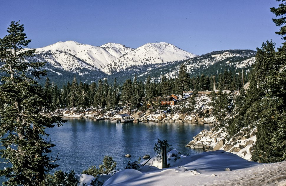 Free image of Lake surrounded by trees and snow-capped mountains