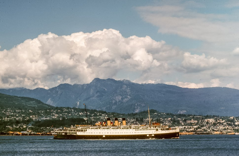 Free image of Vintage Cruise Ship in sea with mountains and city in the background