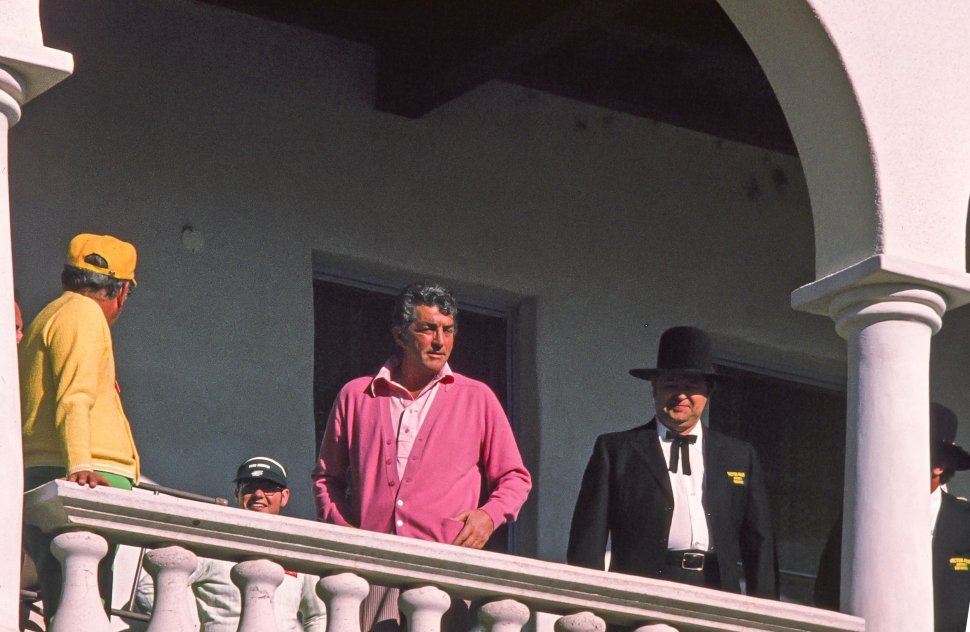 Free image of Dean Martin seen in pink shirt and cardigan as standing in the balcony