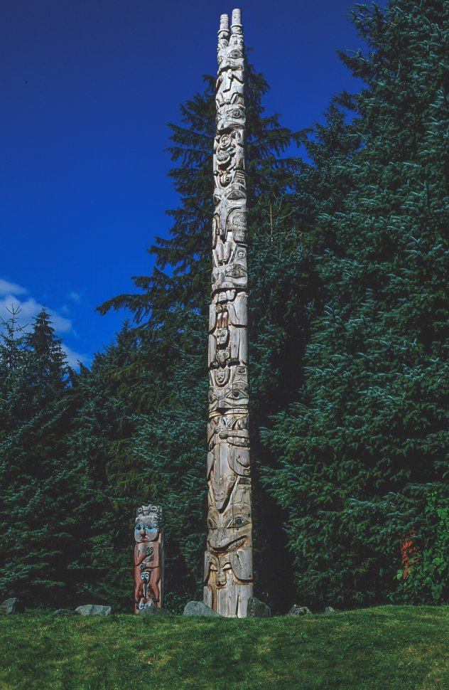 Free image of View of two totem poles in the park