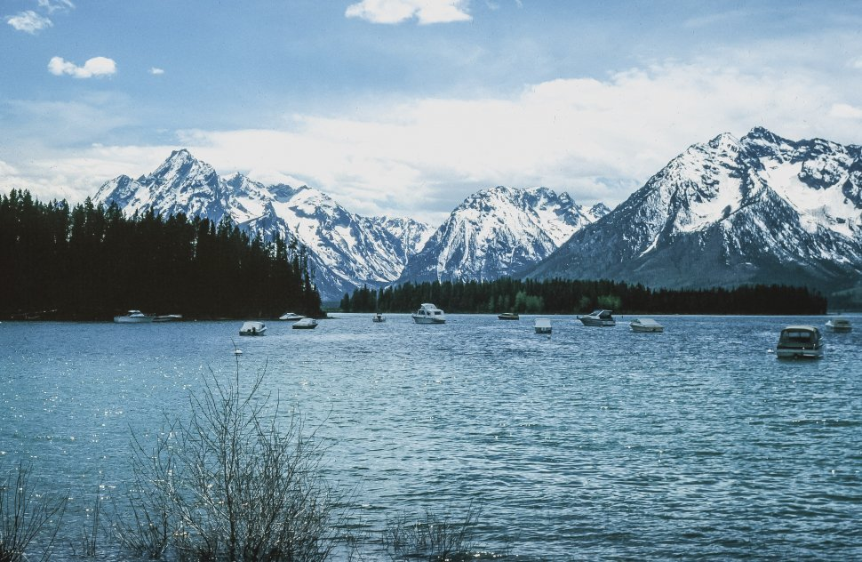 Free image of Scenic View of snow capped mountains with blue lake and boats